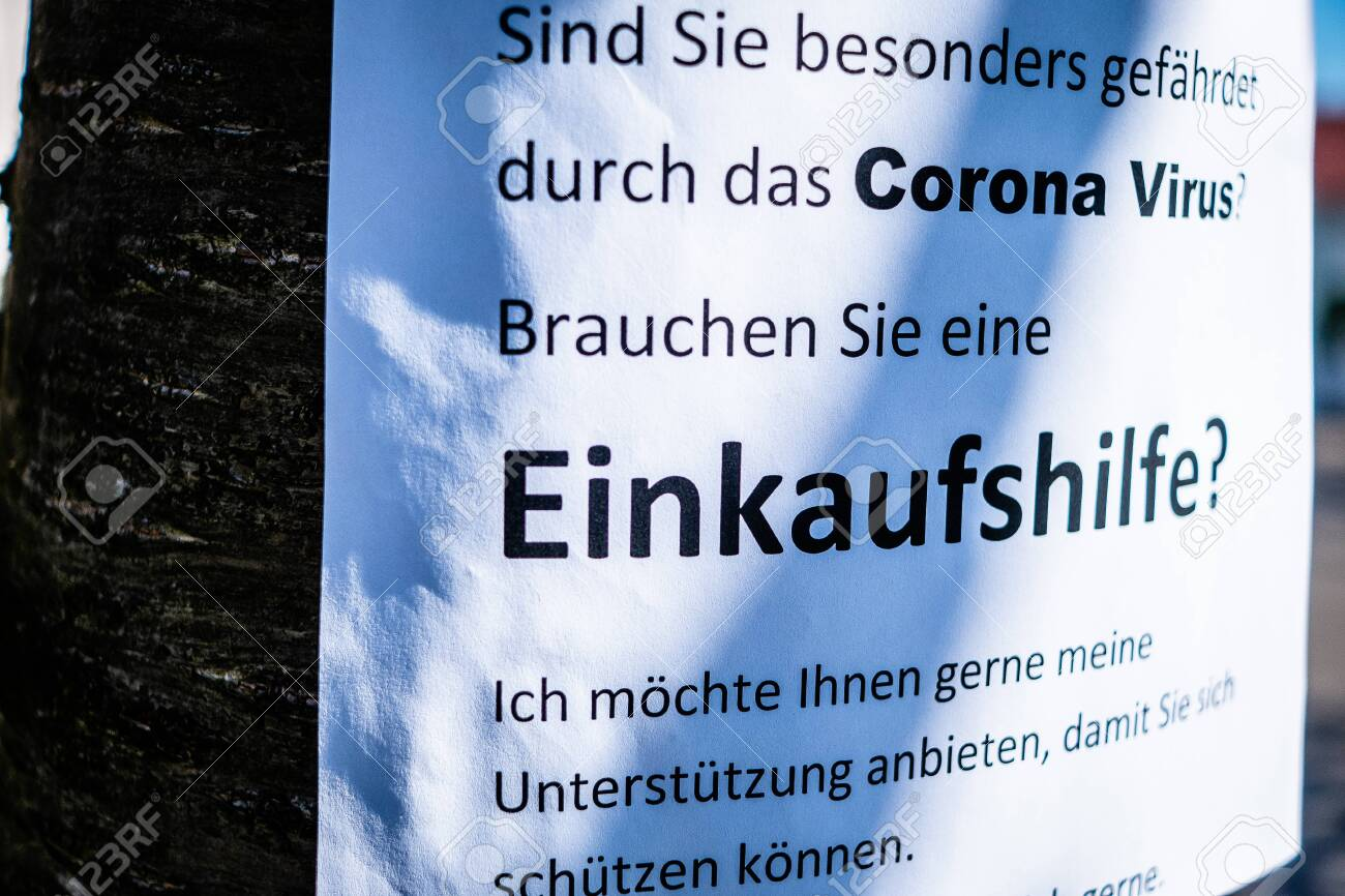 Sign on a tree that offers help for the elderly in the Corona crisis in German Einkaufshilfe für ältere Menschen die besonders gefährdet sind in English Shopping aid for older people who are particularly at risk - 144587381