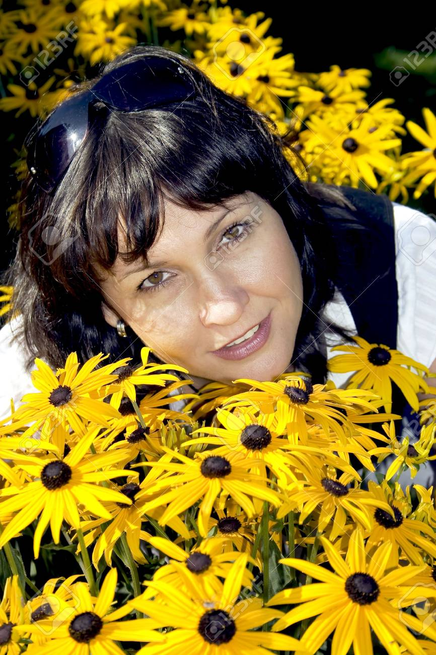 Attractive brunette is in bright yellow flowers Stock Photo - 5371219