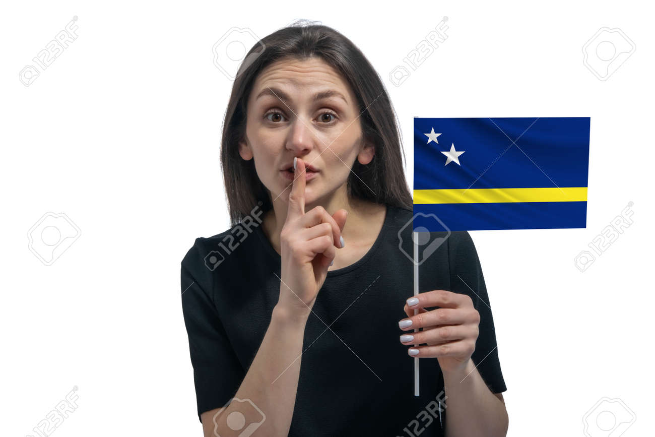Happy young white woman holding flag of Curacao and holds a finger to her lips isolated on a white background - 162935233