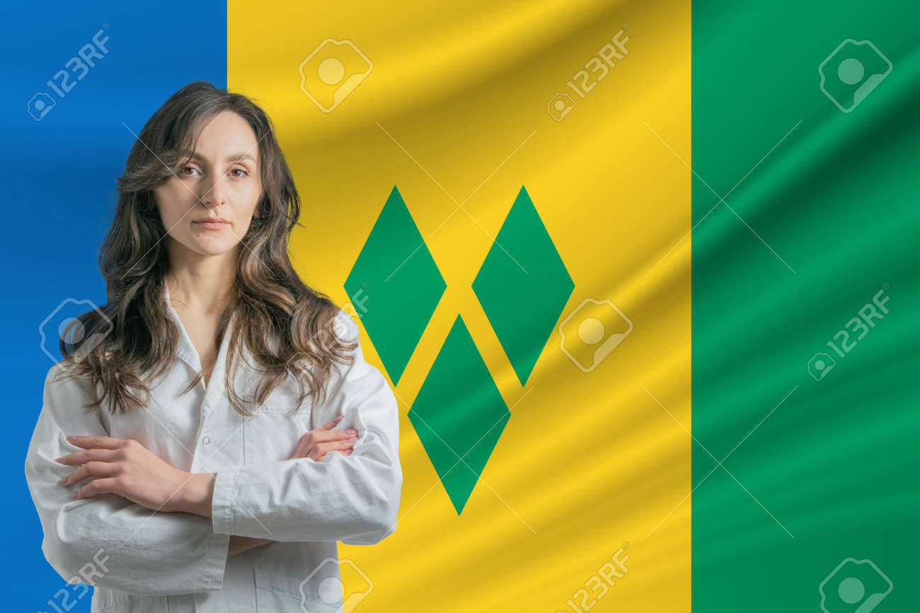 Medicine in Saint Vincent and the Grenadines. Happy beautiful female doctor in medical coat standing with crossed arms against the background of the flag of Saint Vincent and the Grenadines - 171717441