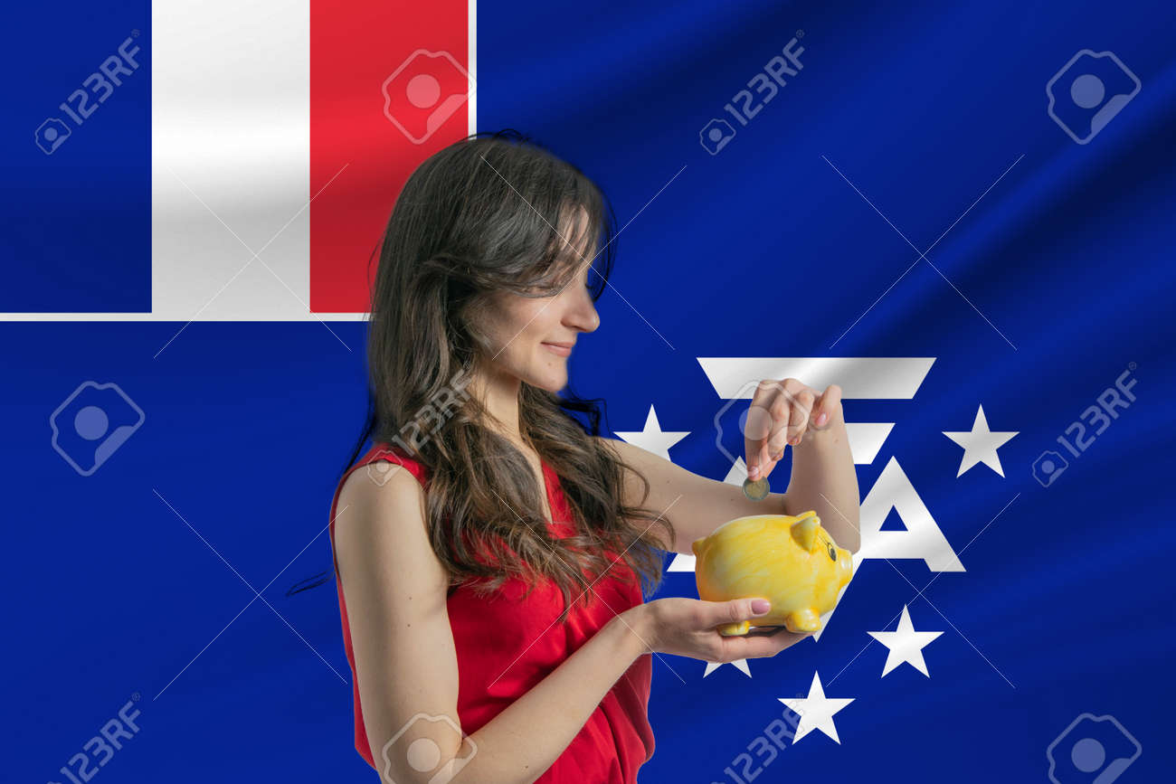 Economy in French Southern and Antarctic Territories. Accumulating and saving money in French Southern and Antarctic Territories. Woman putting money coin in piggy bank for saving money and plan finance - 171717458