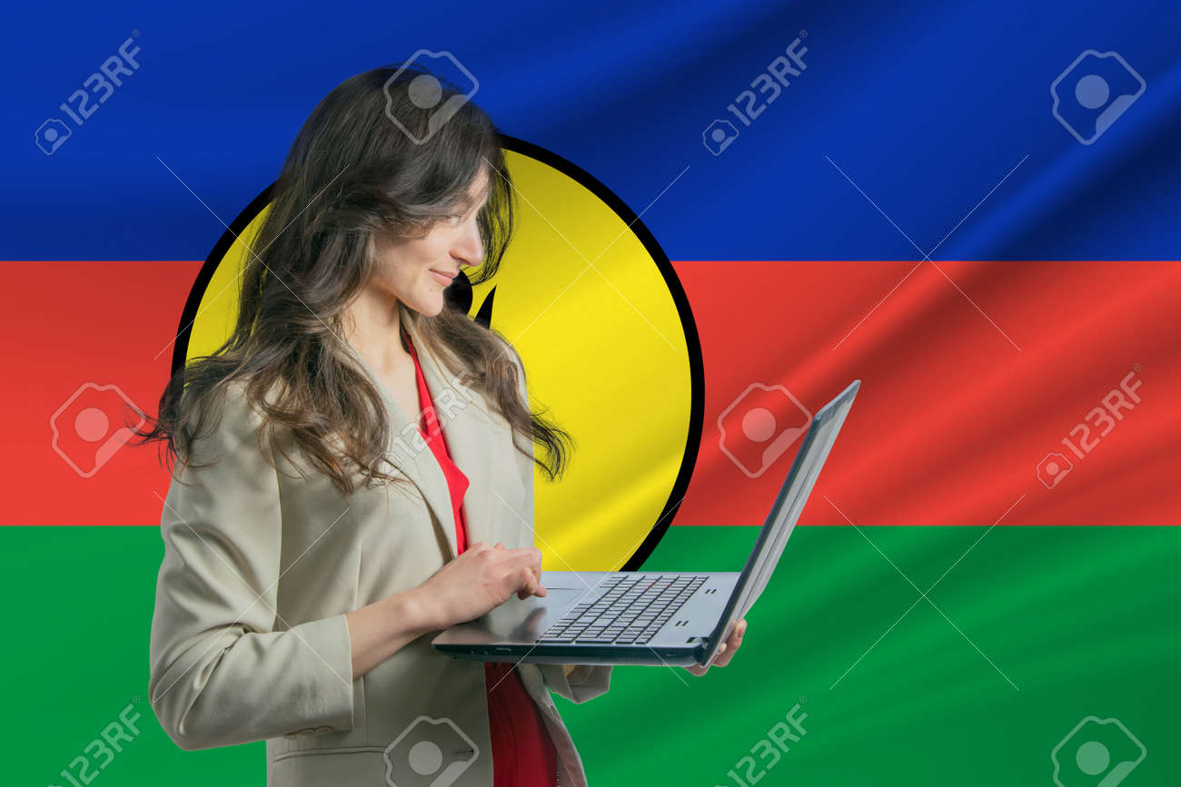 Freelance in New Caledonia. Beautiful young woman freelancer uses laptop computer against the background of the flag of New Caledonia - 171717459
