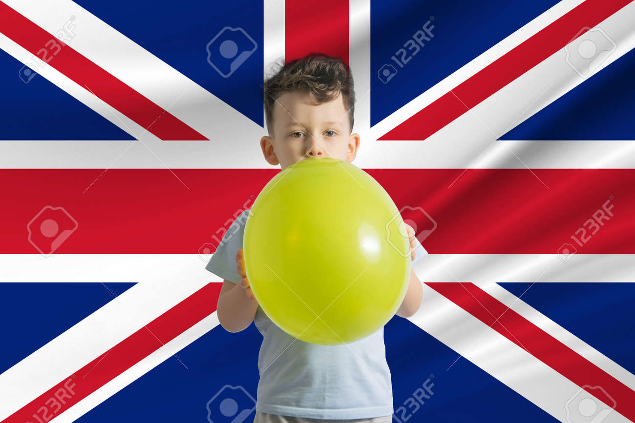 Children's day in United Kingdom. White boy with a balloon on the background of the flag of United Kingdom. Childrens day celebration concept. - 170833865