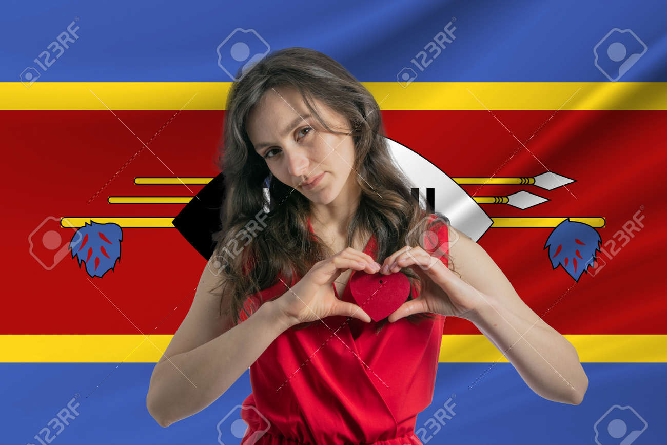 Love Esvatini A girl holds a heart on her chest in her hands against the background of the flag of Esvatini The concept of patriotism. - 171958738