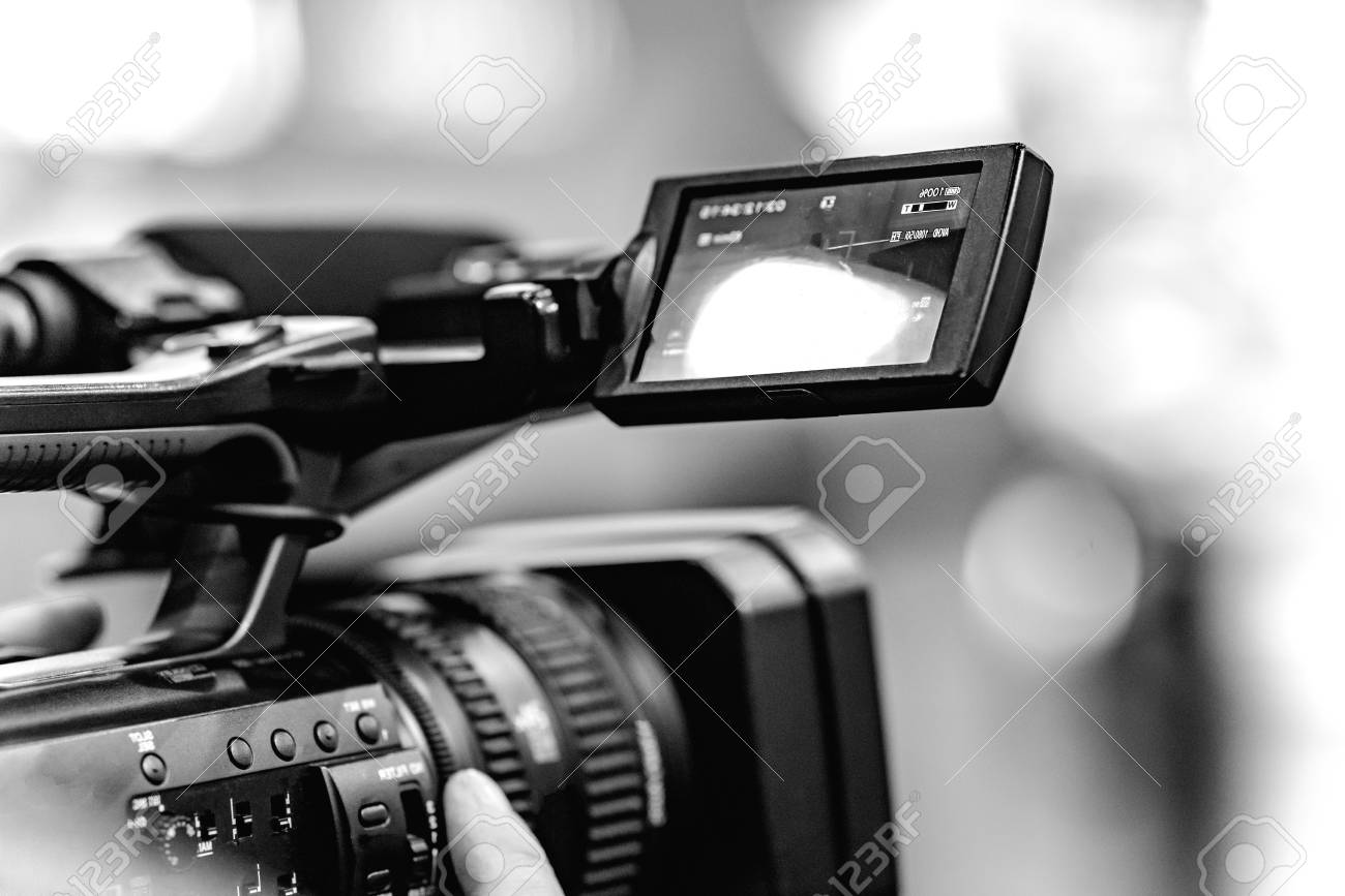Video shooting with a camera with a tripod with a black stabilizer. The background is blurred. - 121365355