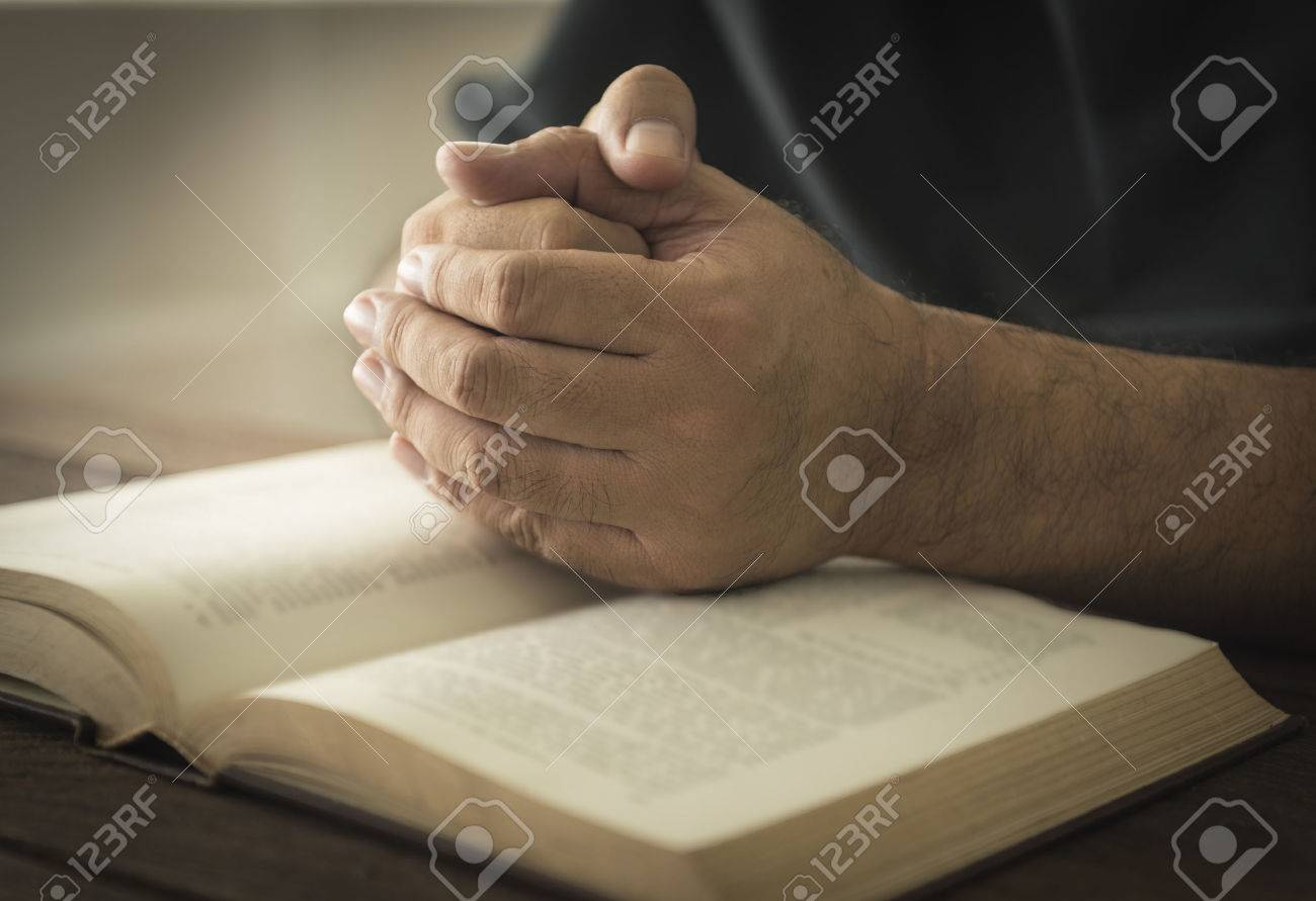 Hands of a man in prayer on a Holy Bible . religion concept - 50003193