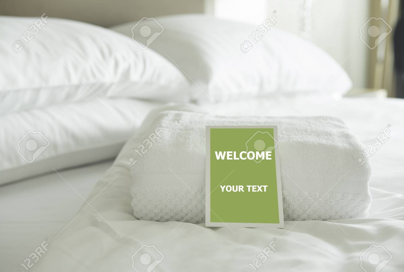 Carte de bienvenue placée dans un lit de chambre d\'hôtel avec pomme verte.
