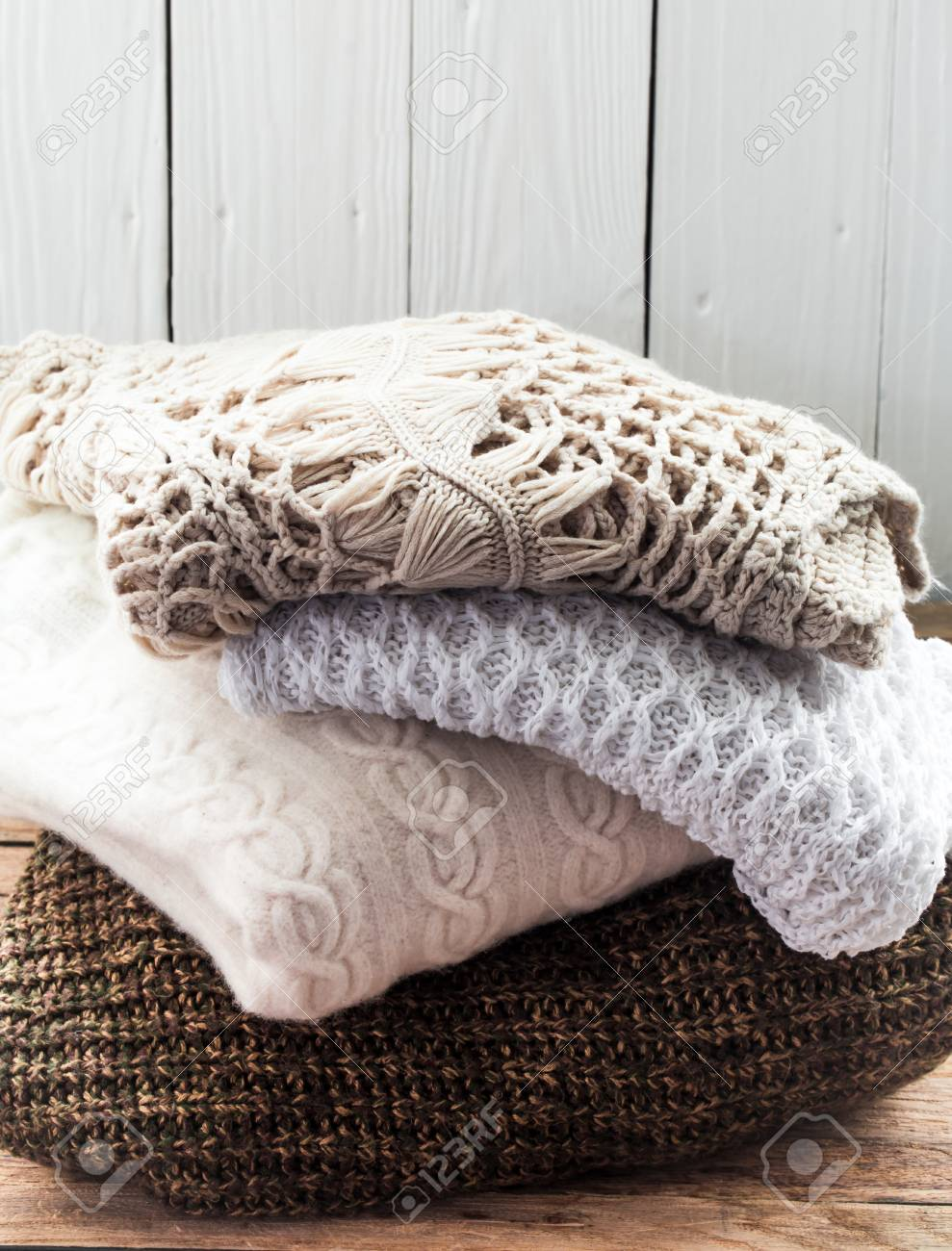0f9591d7d2 Knit cozy sweater folded in a pile on wooden background .Warm the concept  Stock Photo