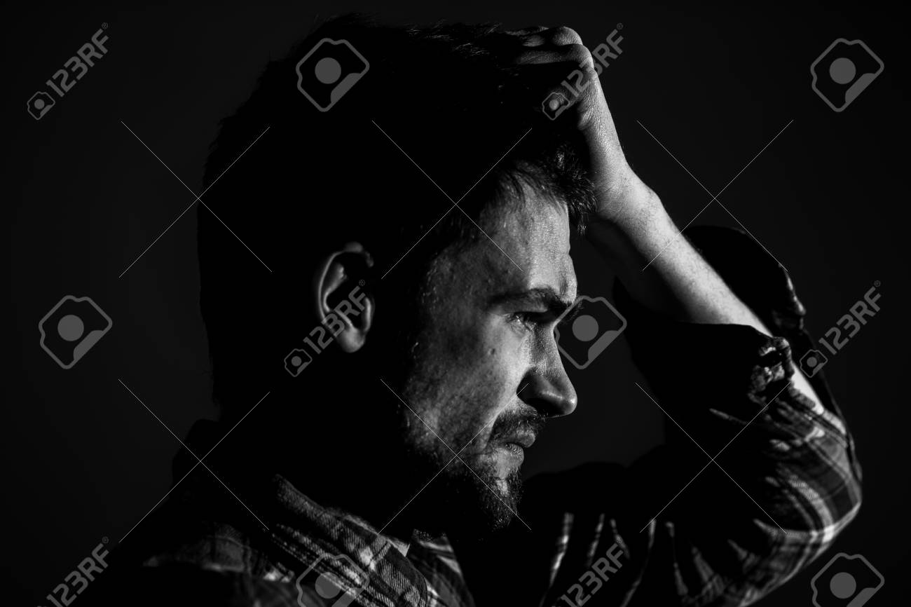 Sad young man on a dark background sad emotions black and white photography