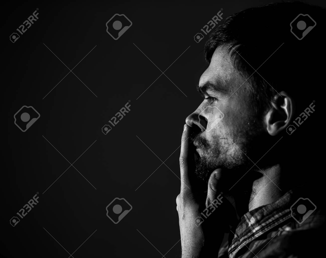 Sad young man on a dark background sad emotions black and white