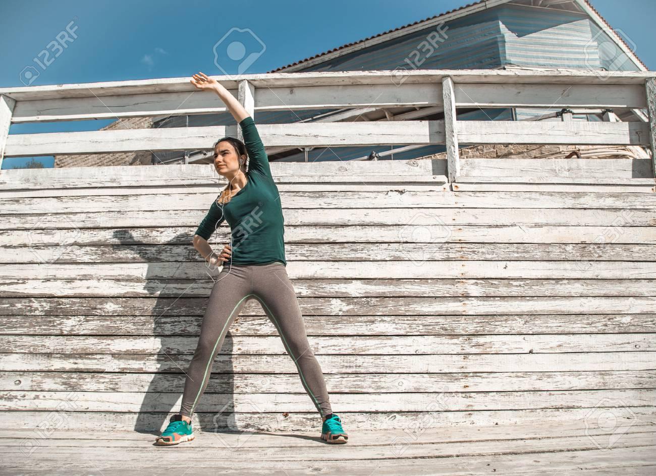 Fitness Sportliche Mädchen In Sportlicher Kleidung Machen Übungen Auf Einem  Hölzernen Hintergrund, Hellen Hintergrund,