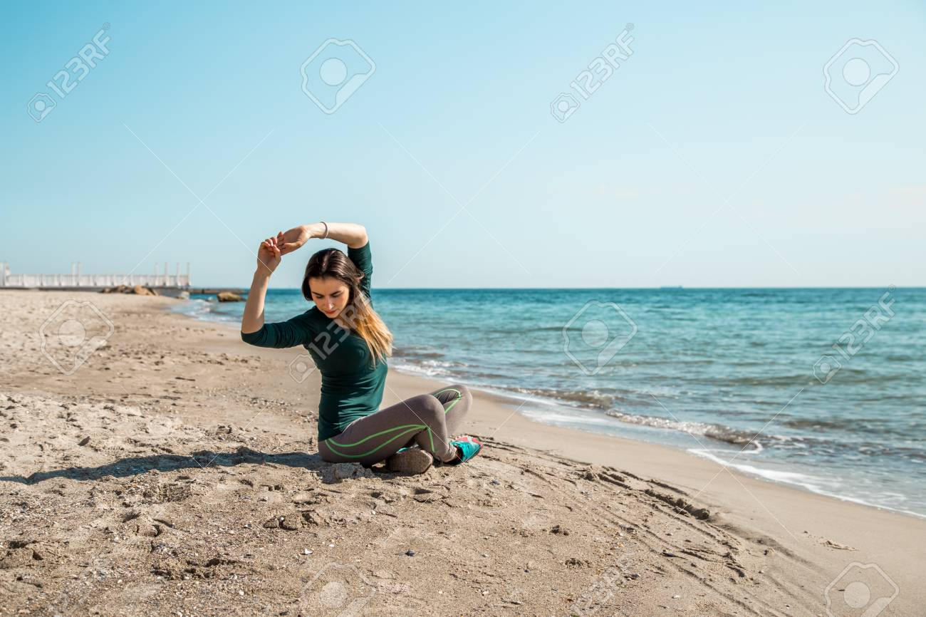 Girl in sportswear fitness by the sea listening to music,sports