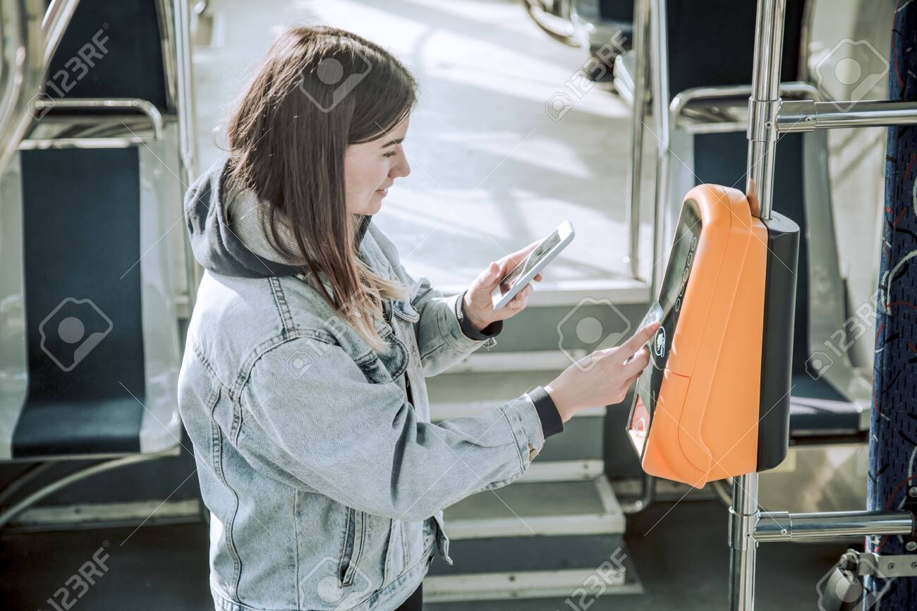 A young woman contactless pays for public transport. Payment by card, Bank transfer . - 132708643