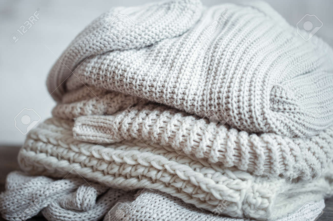 Close up of neatly folded knitted items of pastel color on a light background. - 159096426