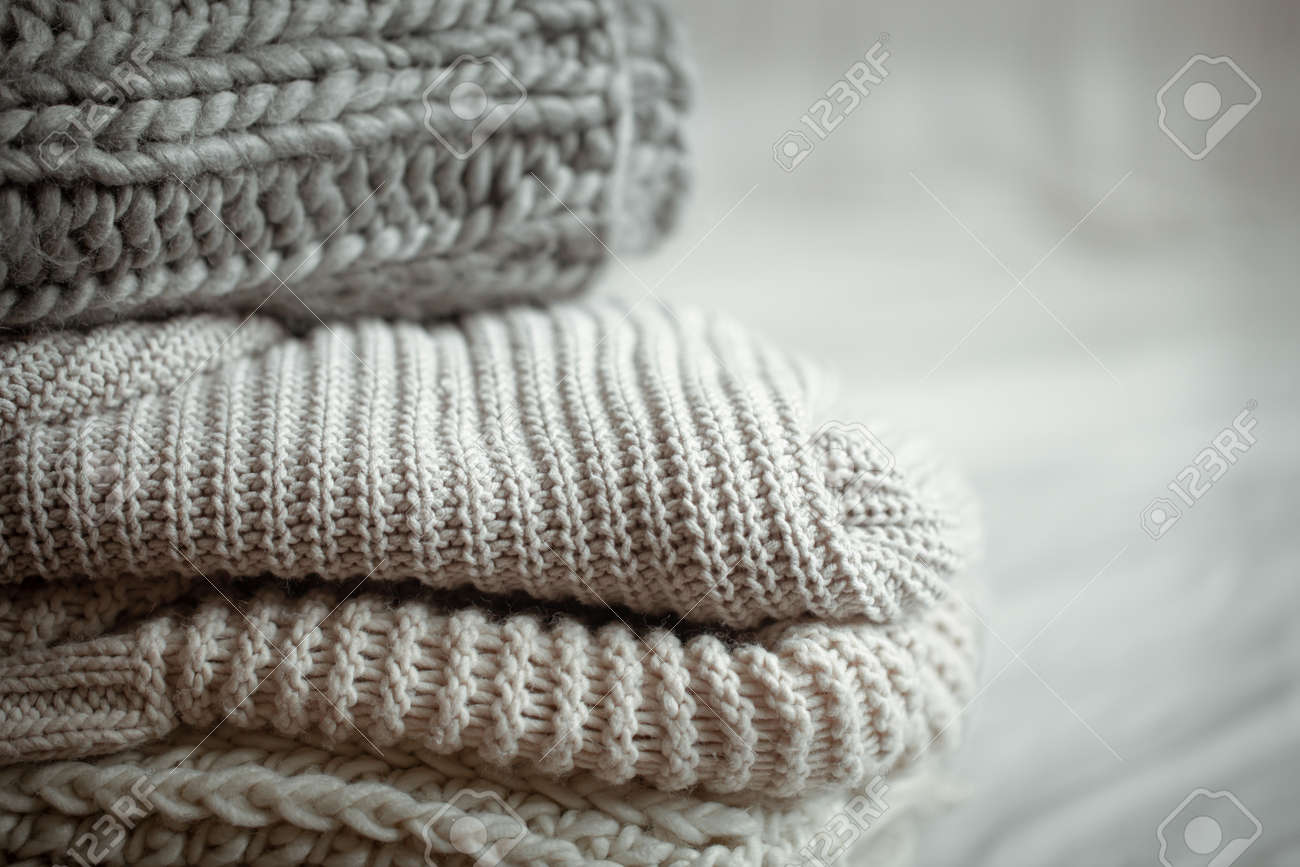Close up of neatly folded knitted items of pastel color on a light background. - 159943282