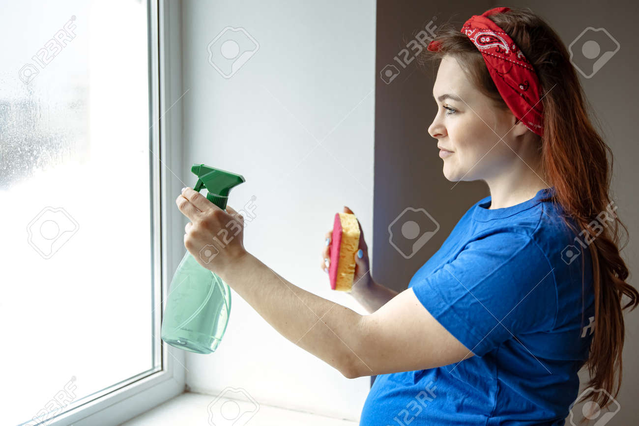 A beautiful pregnant woman in the last months of pregnancy is engaged in cleaning and washes the windows. - 169017489