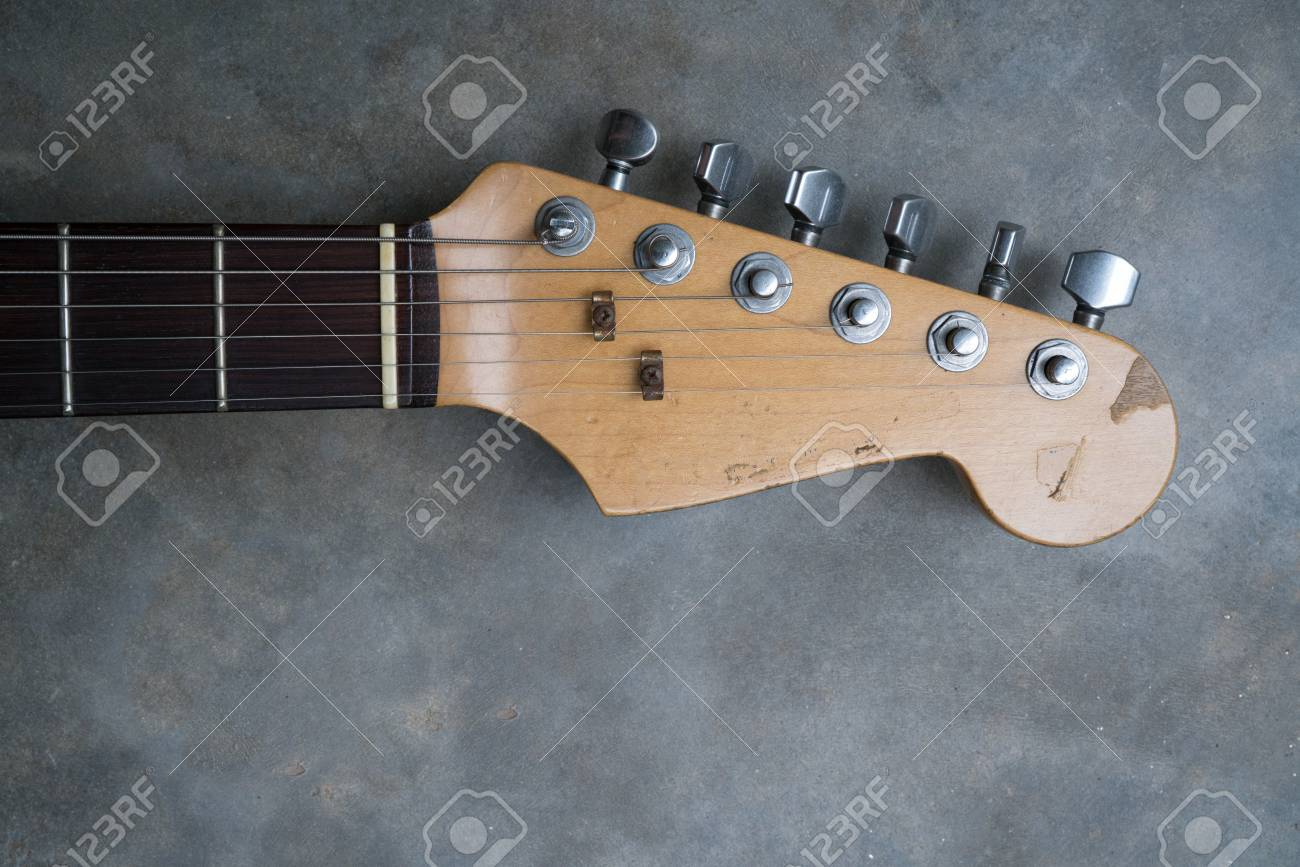 detail of vintage electric guitar headstock on the concrete background
