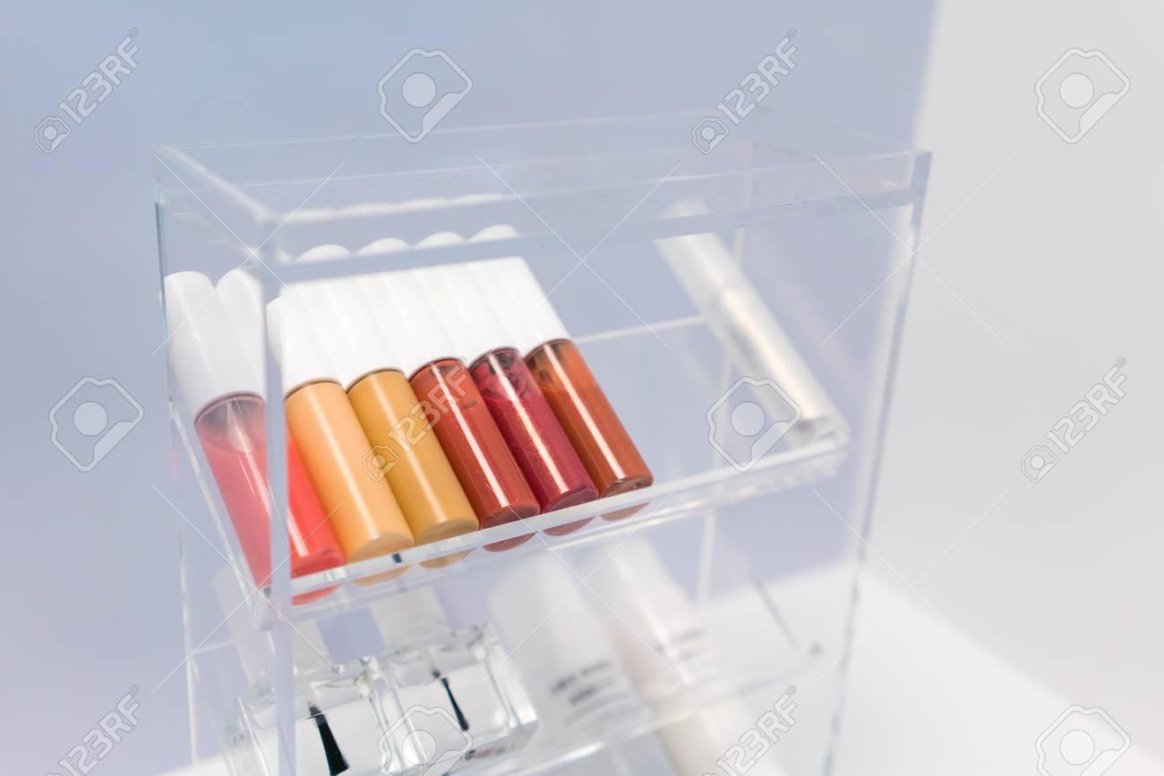 351e75330 Foto de archivo - Una fila de barras de labios de color y revestimiento de  uñas en organizador cosmético de acrílico transparente en la mesa blanca  sobre ...