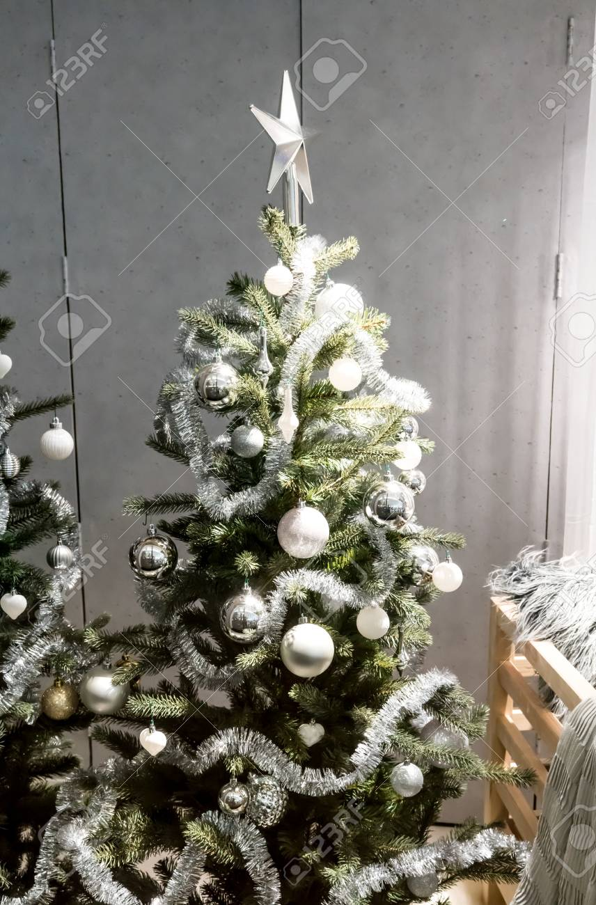 White and silver decorative Christmas tree with tinsel garland,..