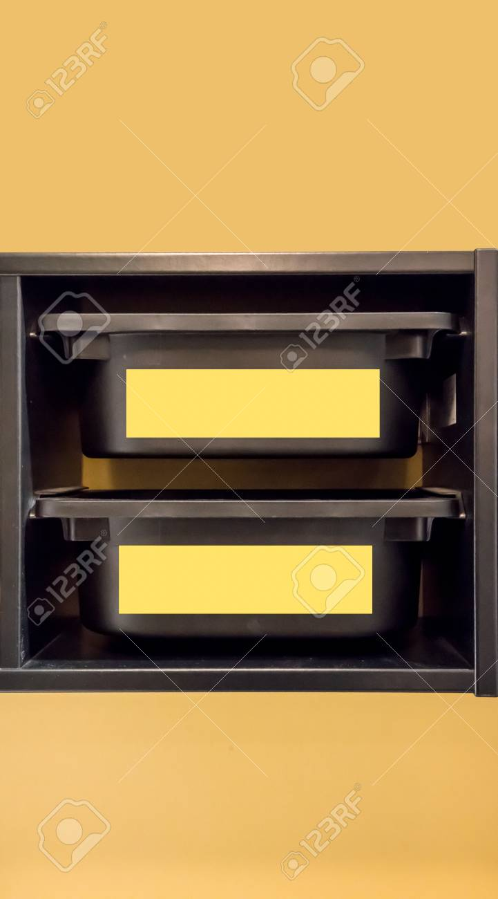 Black Plastic Storage Bin With Yellow Label For Room Organizer Against  Yellow Wall. Stock Photo
