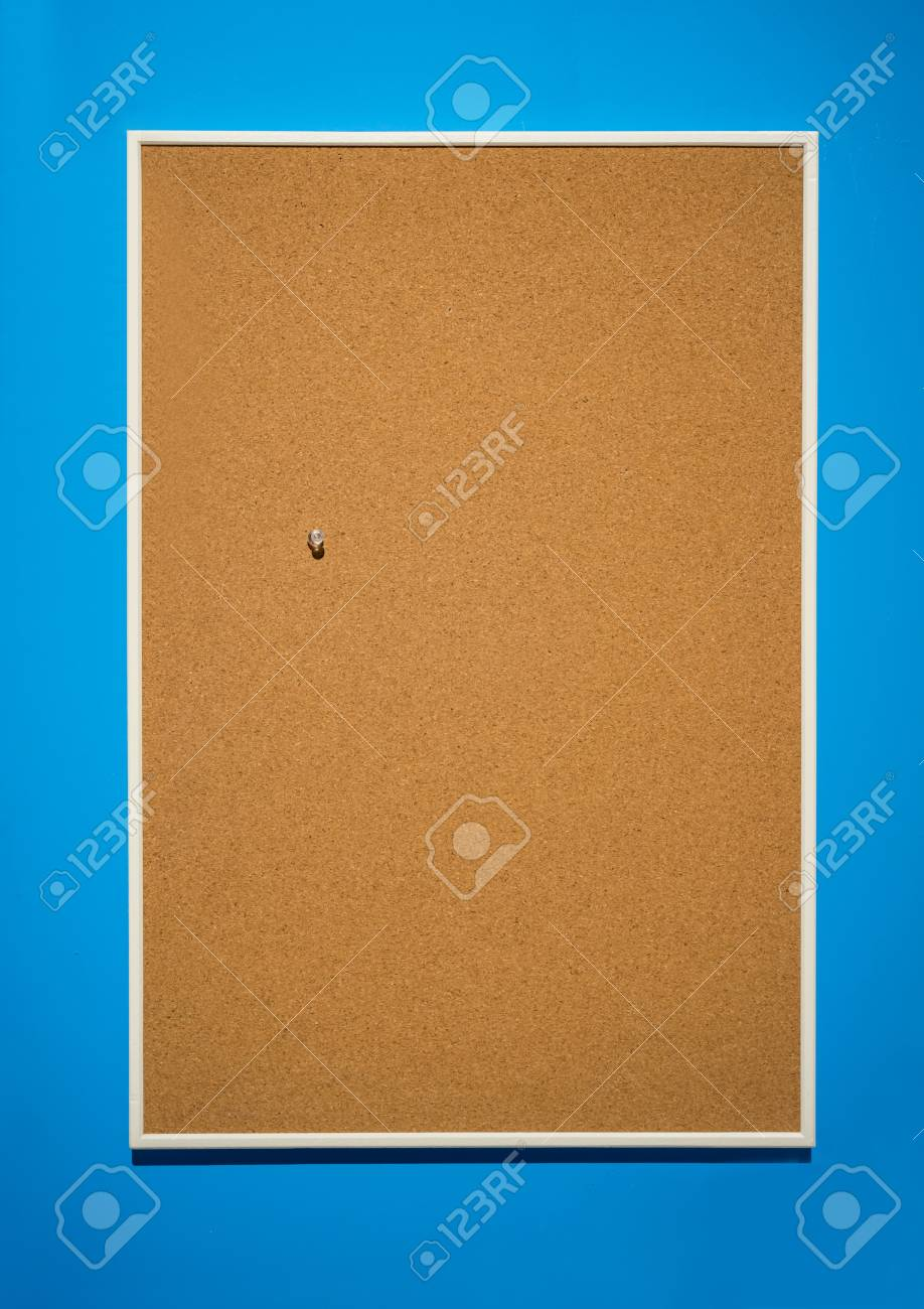Cork Borad Or Notice Board With Wooden Frame Hanging On Blue Wall