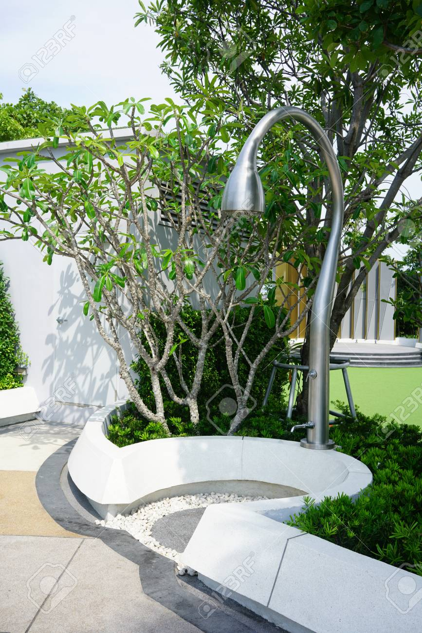 Modern outdoor shower area surrounded by planting within swimming..