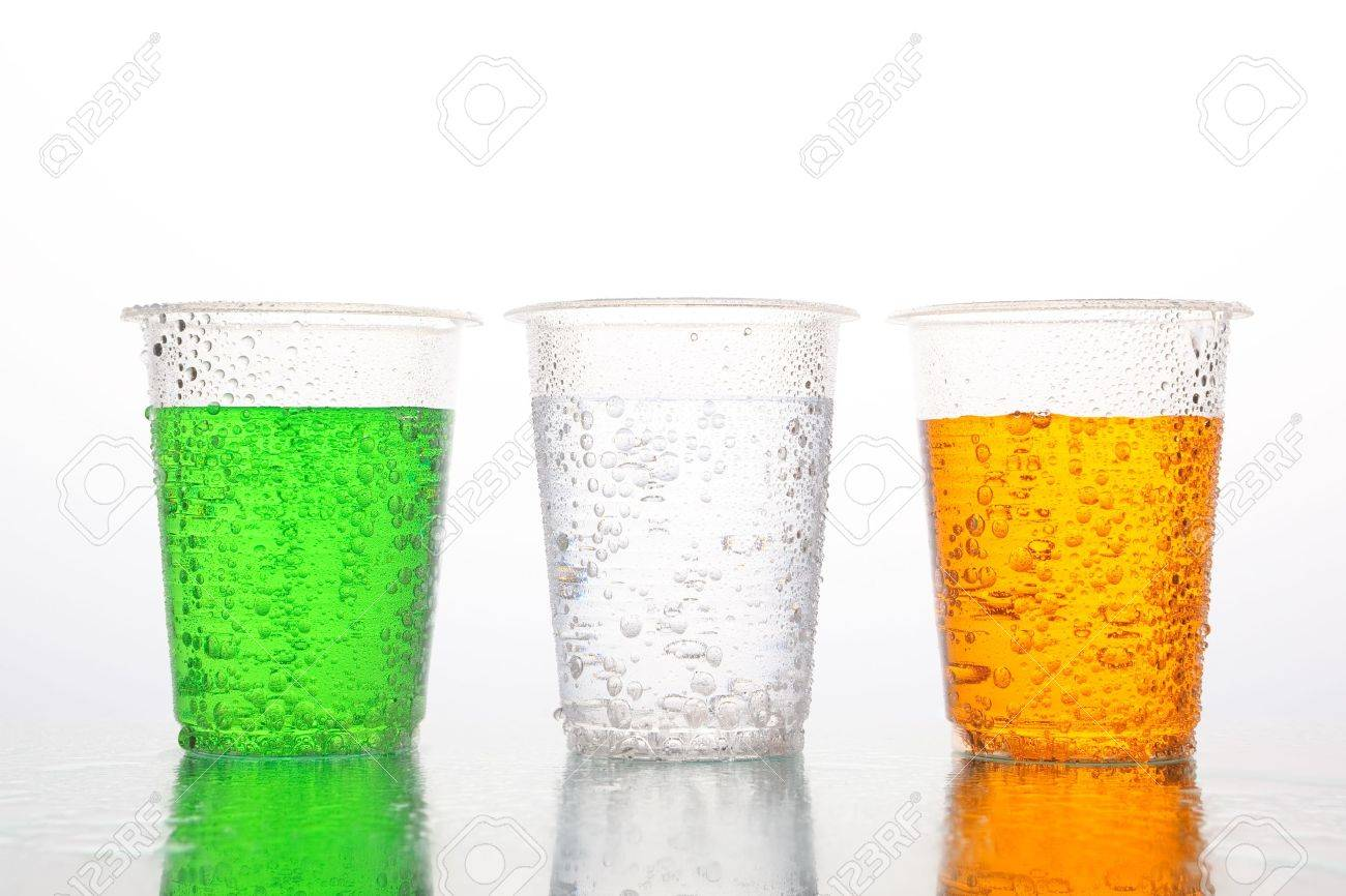 Three plastic cups with different color of carbonated beverages on white background. Green, uncolored and orange drinks. Stock Photo - 8426410
