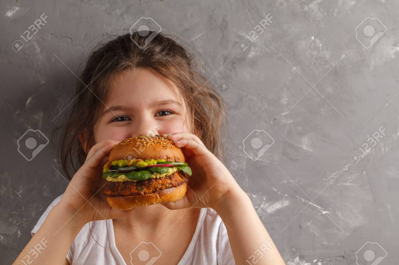 The little girl is eating a healthy baked sweet potato burger