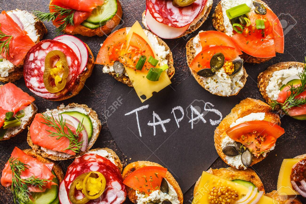 Assorted spanish tapas with fish, sausage, cheese and vegetables. Dark background, flat lay. - 116789809