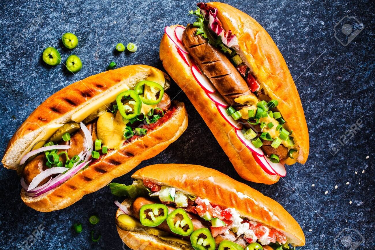 Hot dogs with different toppings on a dark blue background, food flat lay. Fast food concept. - 131188679