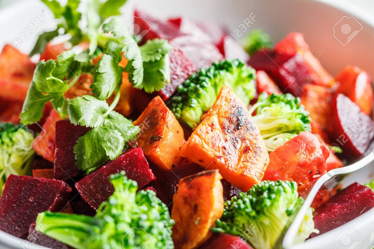 Baked sweet potato, beetroot and broccoli salad in a white bowl. - 141616877