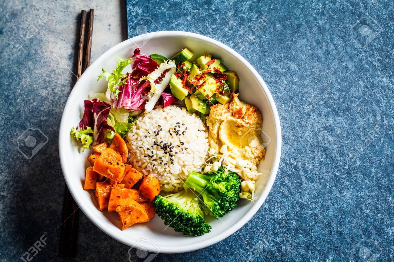Buddha bowl. Vegan rice and vegetables salad. Macrobiotic set with rice, hummus, avocado, broccoli and sweet potato. - 141616975