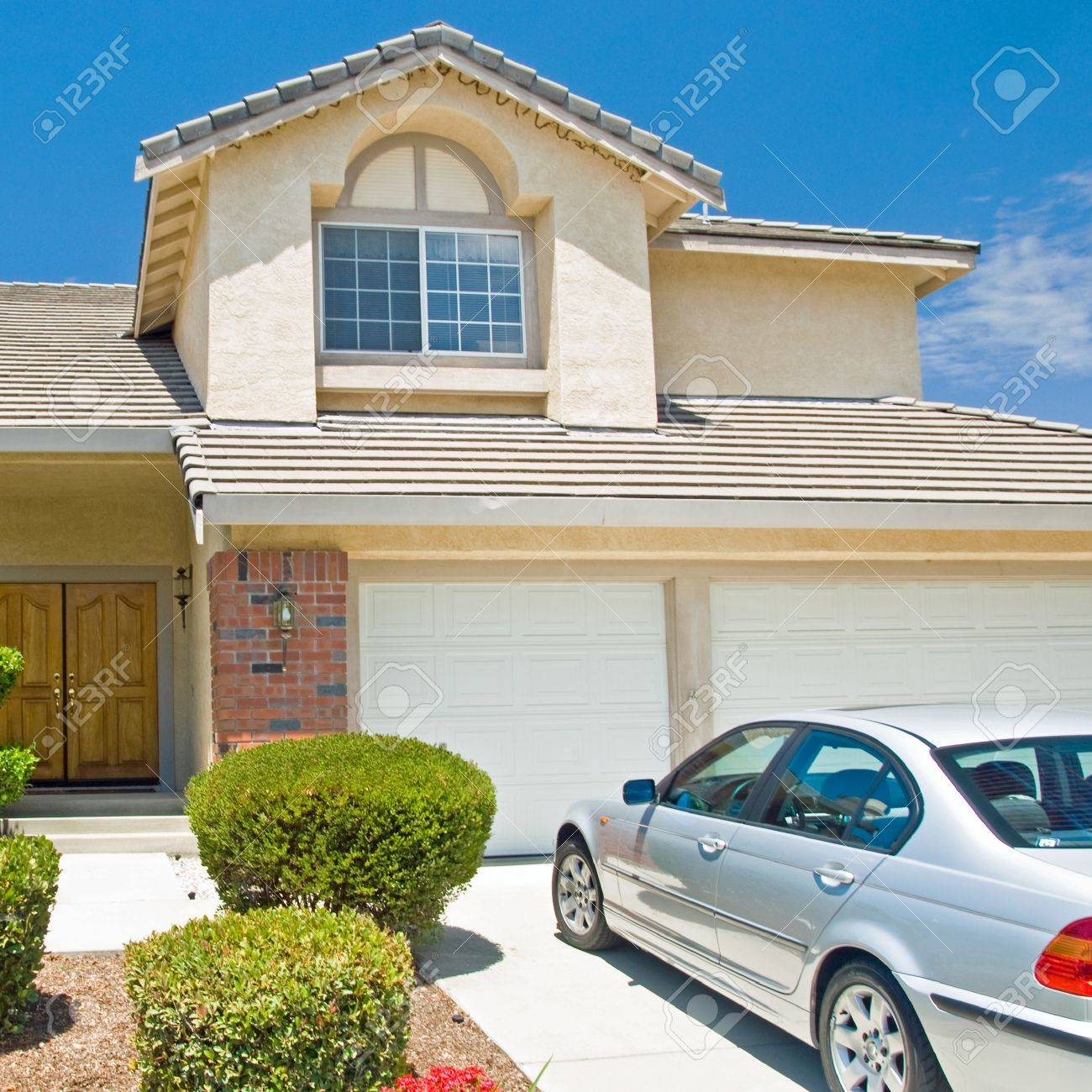 New American dream home with a beautiful blue sky in background and brand new car parked outside. Stock Photo - 18479343