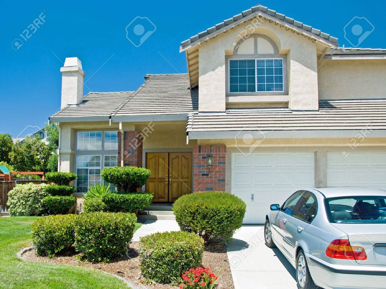 New American dream home with a beautiful blue sky in background and brand new car parked outside. Stock Photo - 18509649