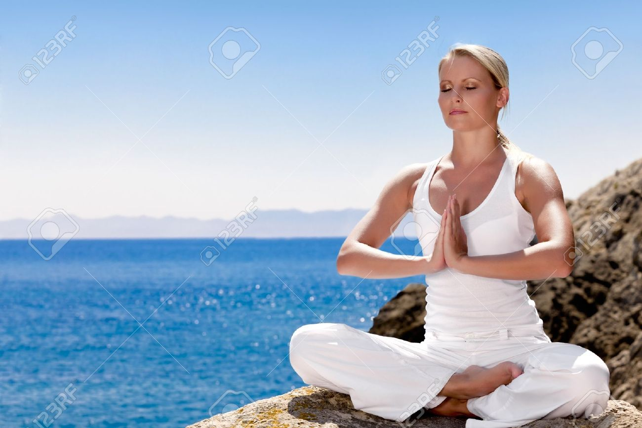 Beautiful positive girl clothing in white sit at the seaside on the rock and meditating in yoga pose Stock Photo - 12508307