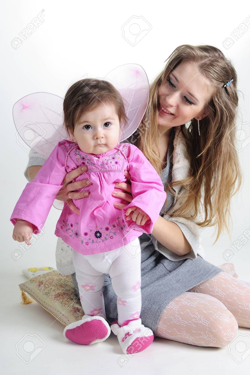 The small beautiful girl at mum on hands on a white background with wings Stock Photo - 12732614