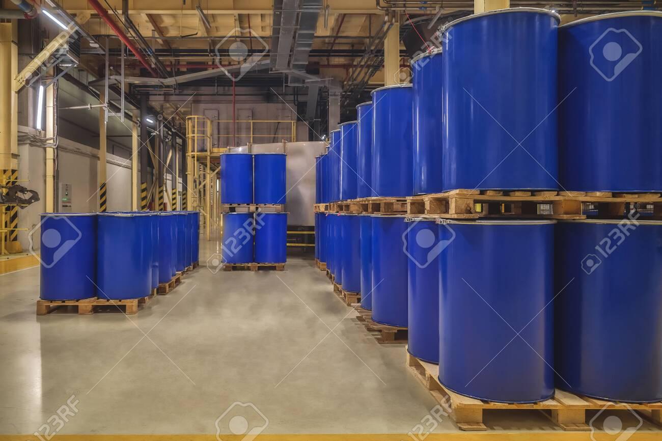 Blue metal barrels. Chemical industry. Metal barrels for chemicals. Storage racks. Barrels are stored in a warehouse. Warehouse storage. - 138688227
