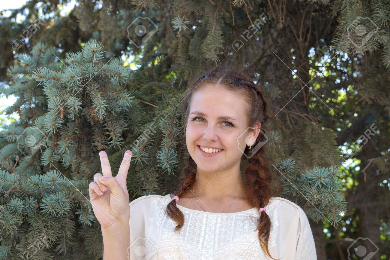 girl of slavic appearance against a fir tree stock photo picture