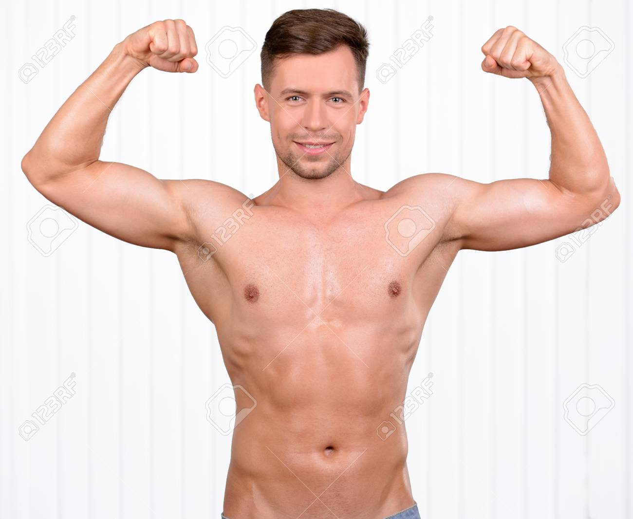 56371688c Keeping his body in good shape. Cheerful young muscular man demonstration  of his body Stock