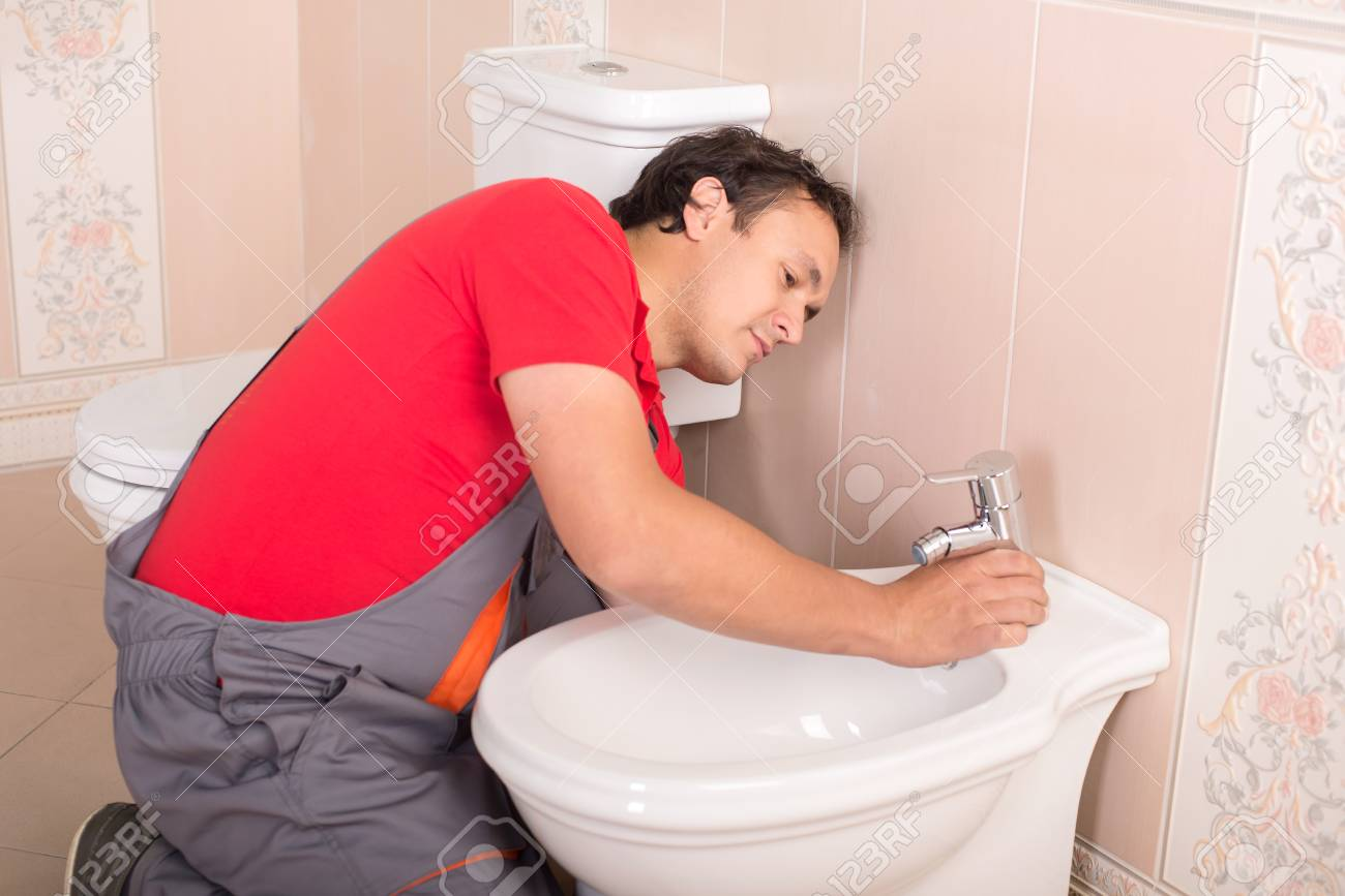 Plumber During His Work In The Toilet. Stock Photo, Picture And ...