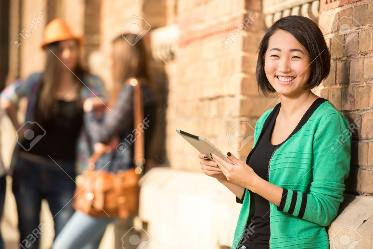 Beautiful asian female student with tablet at the college, outdoors. Stock  Photo - 32994093