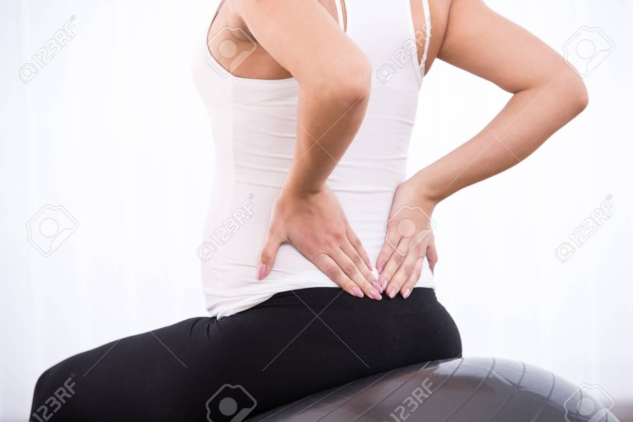 Foto de archivo - La mujer embarazada está haciendo ejercicios con pelota  de gimnasia. Fondo blanco. e512a7570c74