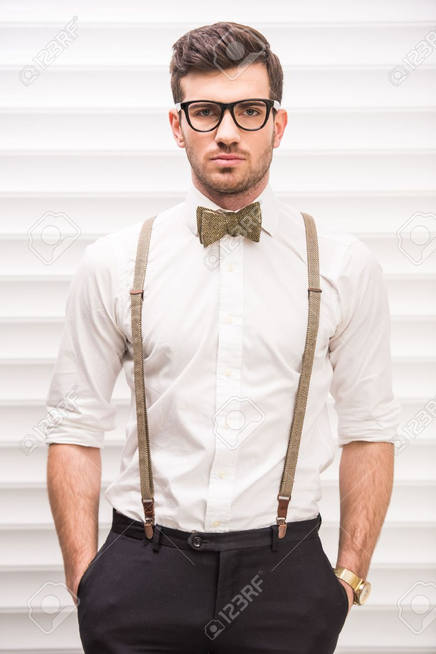 710290568efc Portrait of a handsome guy with glasses, suspenders and bow-tie. Stock Photo