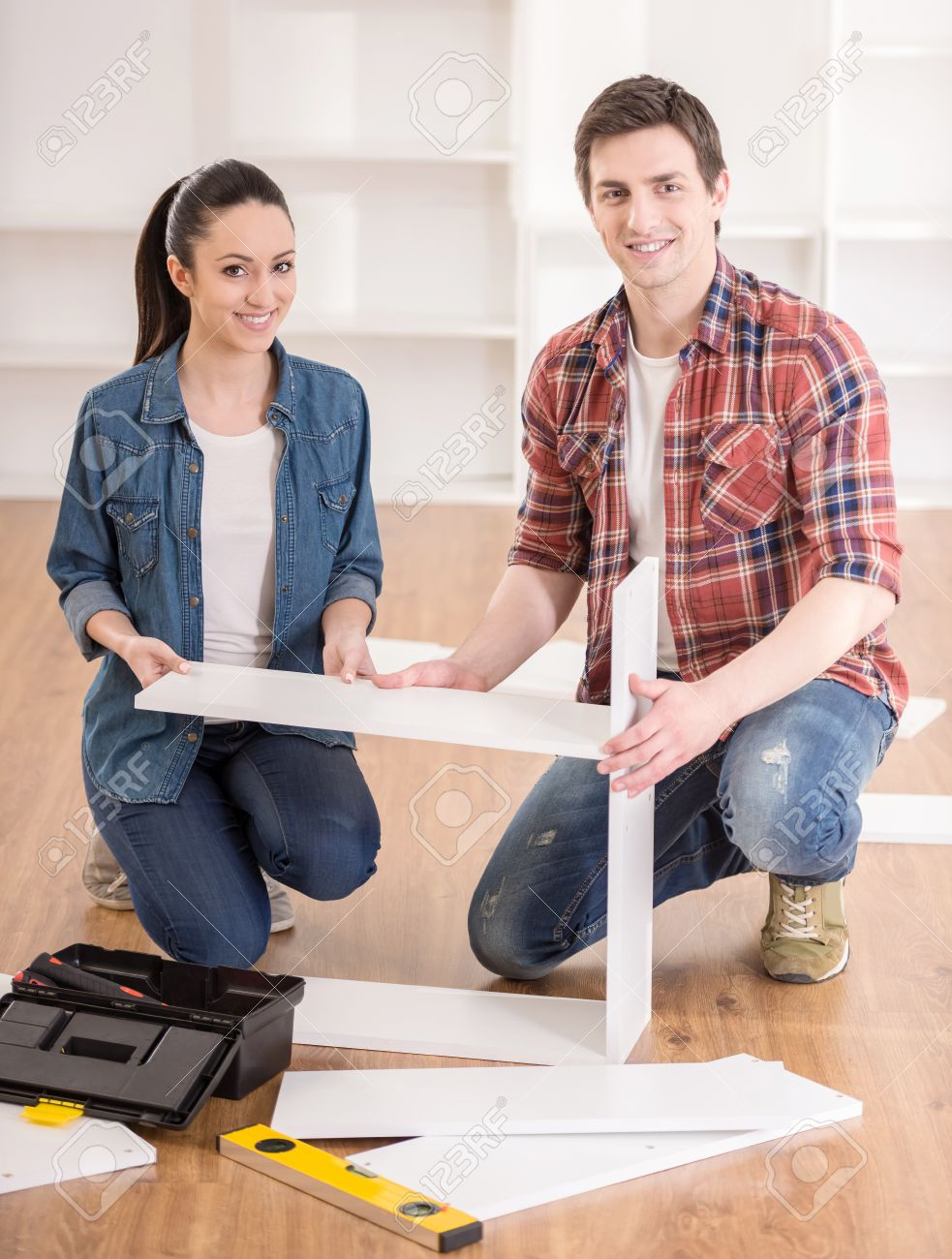 Happy Young Couple Putting Together Self Assembly Furniture As They Move  Into Their New House.