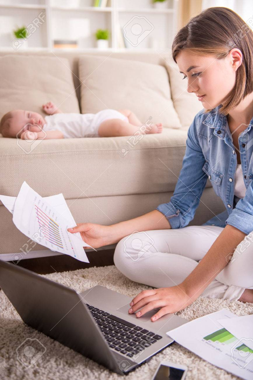 Young woman is working at home while her little baby is sleeping. Standard-Bild - 48104050