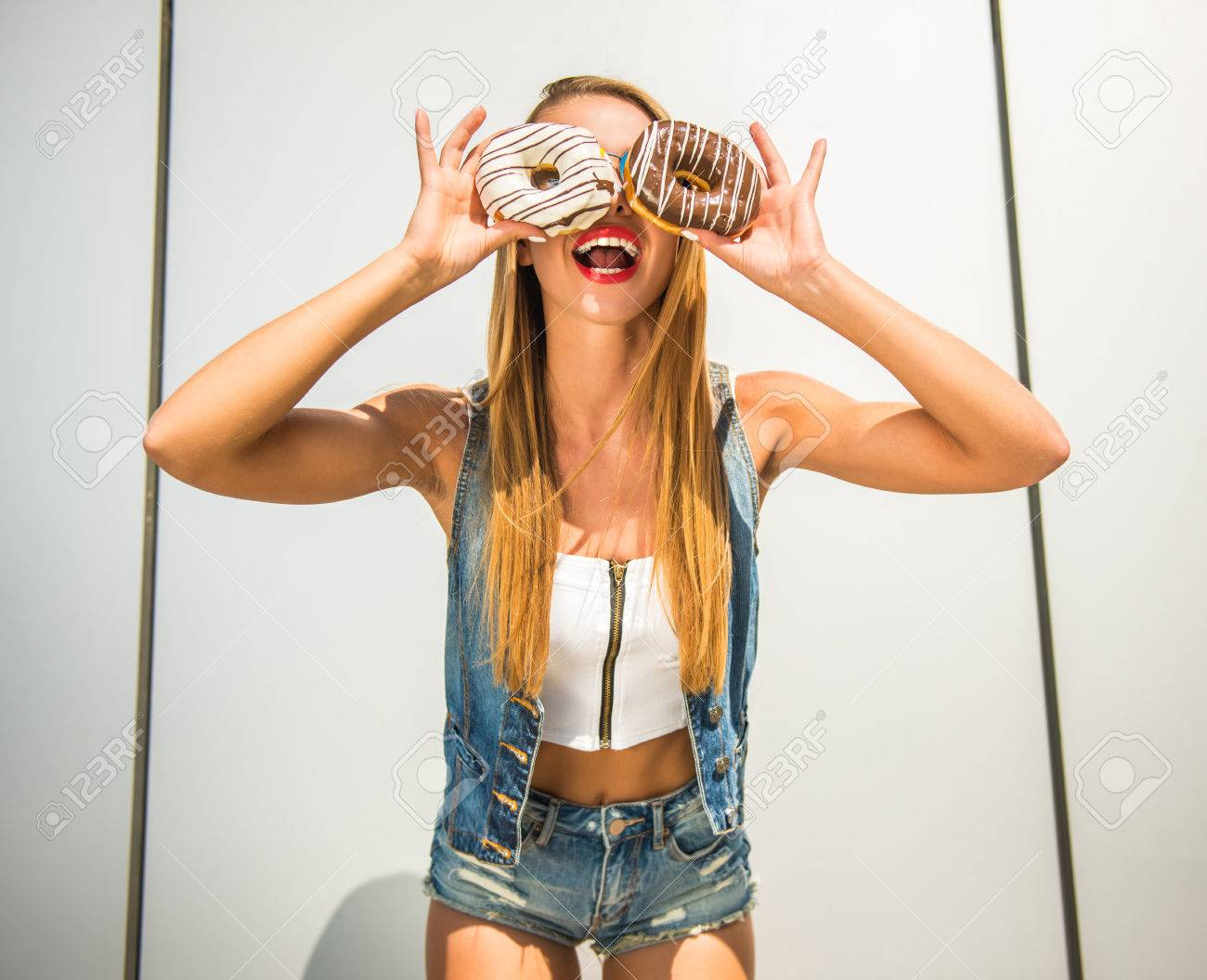 Playful young woman holding donuts against her eyes and smiling while standing against the wall. Standard-Bild - 48107616