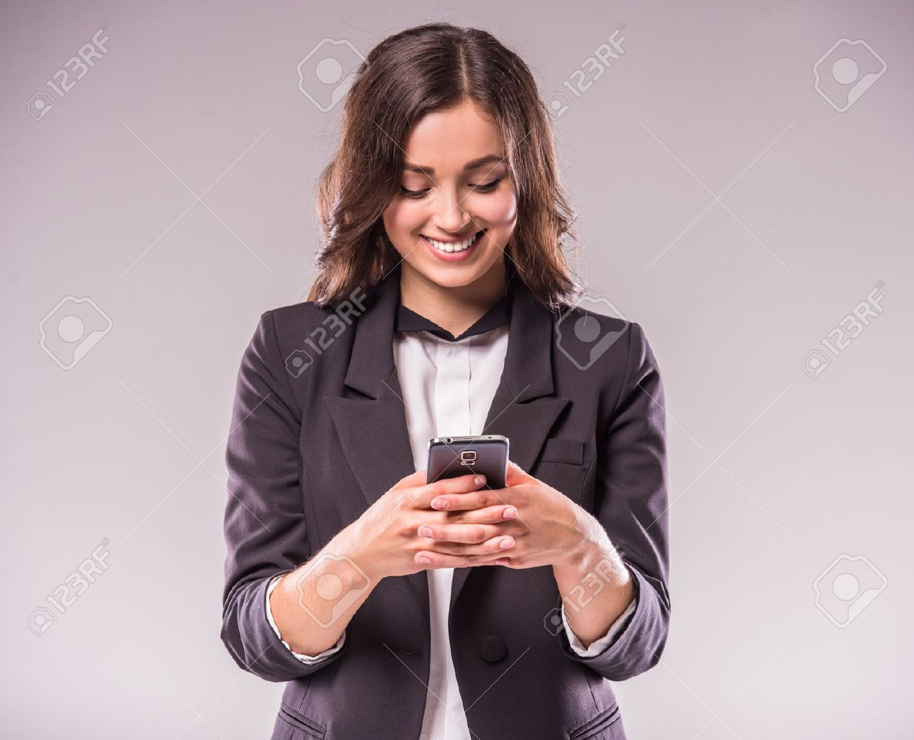 Young woman is writing a message with smartphone, standing on grey background. Standard-Bild - 48108212