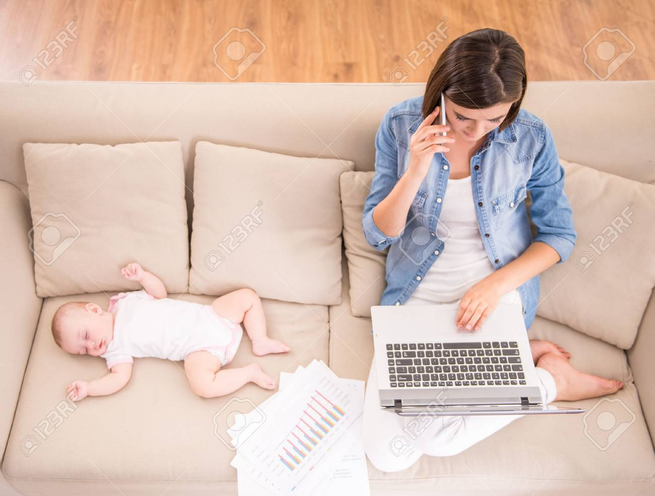 Top view of young woman is working at home while her little baby is sleeping. Standard-Bild - 48108677
