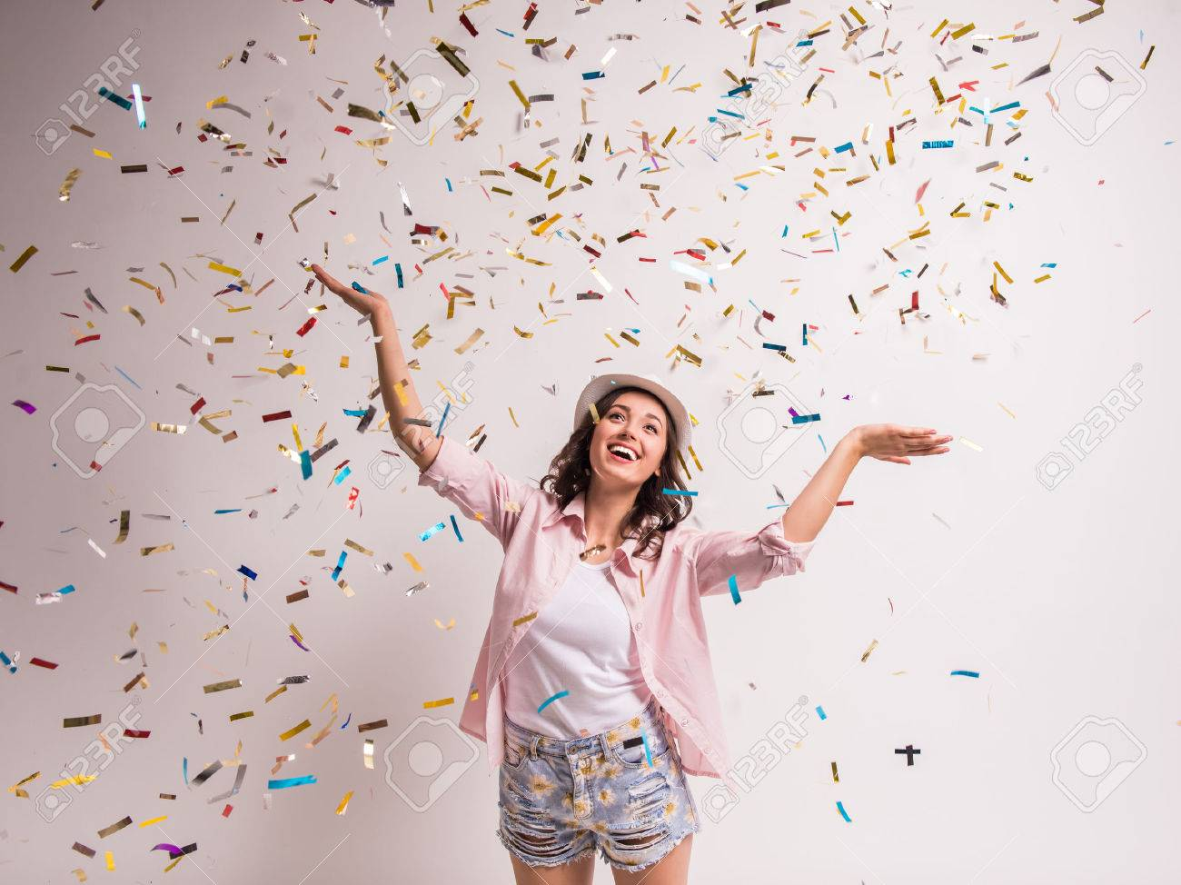 Cheerful young woman is stretching out her hands while confetti falling on her. Standard-Bild - 48109706