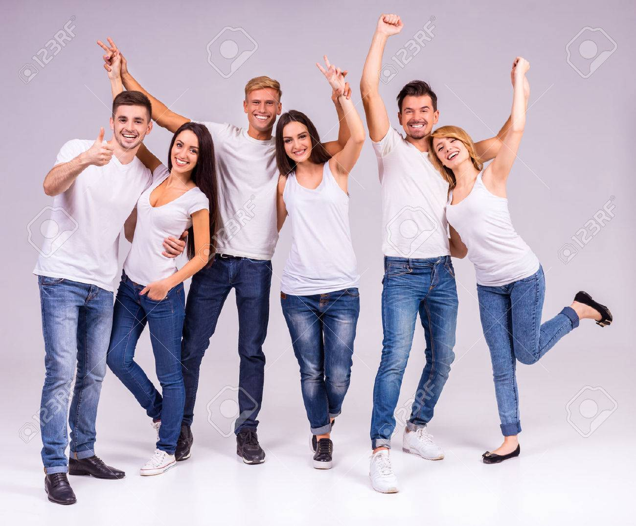 A group of young people smiling on a gray background. Studio shooting Standard-Bild - 46490775